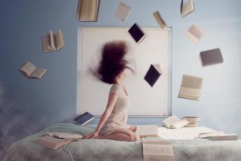 Jente i en seng med masse bøker rundt seg, foto: Pexels fra Pixabay